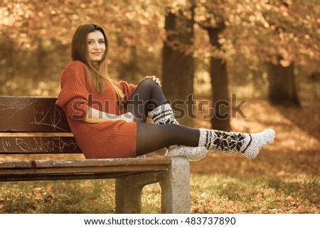 Nature outdoor relax leisure scenery concept. Redhead lady chilling on bench. Young elegant girl sitting in autumnal park.