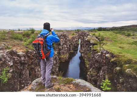 nature photographer, hiker with backpack taking photo of beautiful landscape in Iceland national park Thingvellir