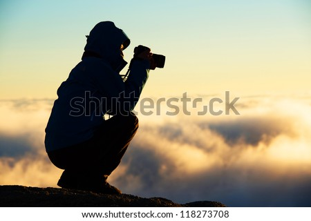 Nature photographer shooting in the mountains - stock photo