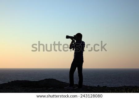Nature photographer shoots the setting sun. Near Agia Pelagia Town, Crete Island, Greece - JUNE 19, 2013 - stock photo