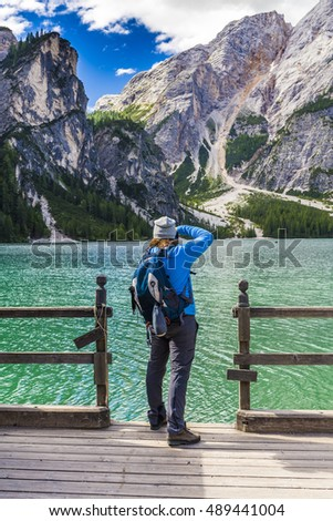 Nature photographer tourist with camera shoots while standing on the edge of wharf near Lago di Braies (Pragser Wildsee). Beautiful Dolomites Nature , Italy
