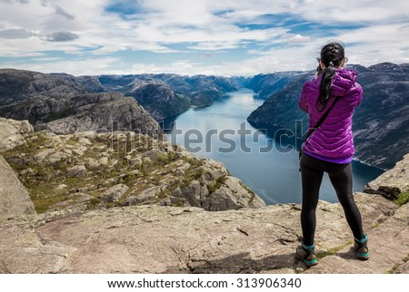 Nature photographer tourist with camera shoots while standing on top of the mountain. Beautiful Nature Norway Preikestolen or Prekestolen. - stock photo