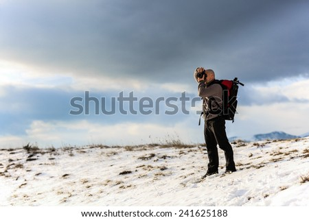 Nature photographer trekking in the mountains winter