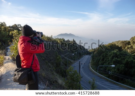 Nature photographer with digital camera on the mountain - soft focus - stock photo
