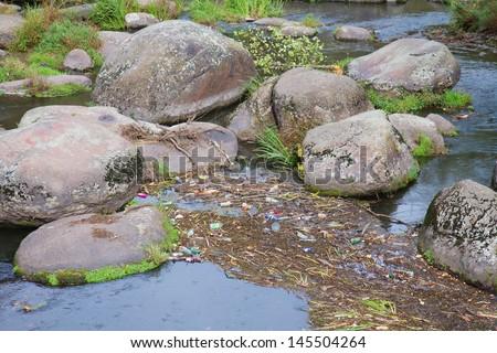 Nature pollution, garbage in the river, Korosten, Ukraine - stock photo