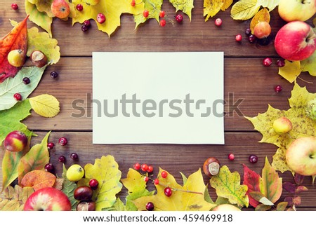 nature, season, advertisement and decor concept - close up of white paper sheet in frame of autumn leaves, fruits and berries on wooden table - stock photo