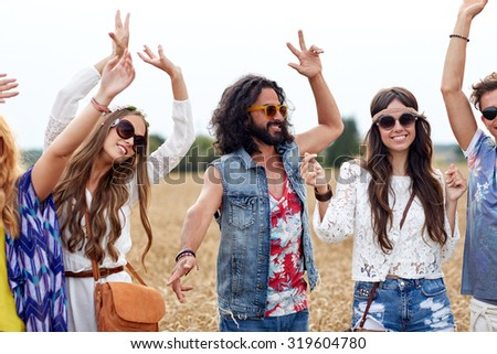 nature, summer, youth culture and people concept - happy young hippie friends dancing on cereal field - stock photo