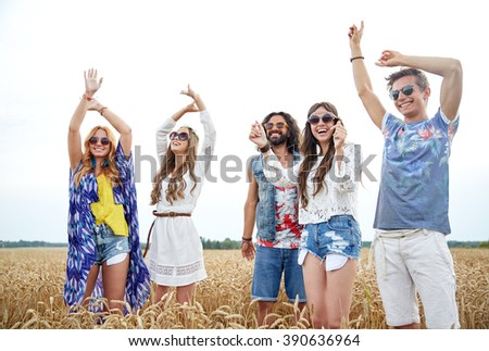 nature, summer, youth culture and people concept - happy young hippie friends dancing outdoors - stock photo