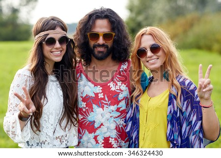 nature, summer, youth culture, gesture and people concept - smiling young hippie friends in sunglasses showing peace hand sign on green field - stock photo