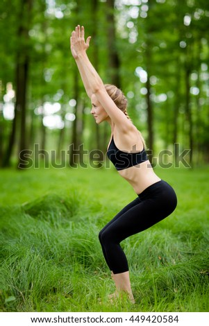 Nature yoga session in beautiful green polish woods, between trees. Utkatasana, chair pose