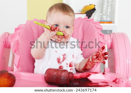 Naughty baby eating alone in the high chair - stock photo