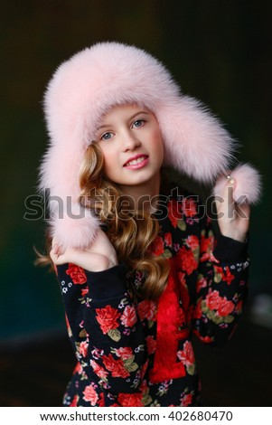 naughty blond girl in a bright pink sweater and a fur hat smiling