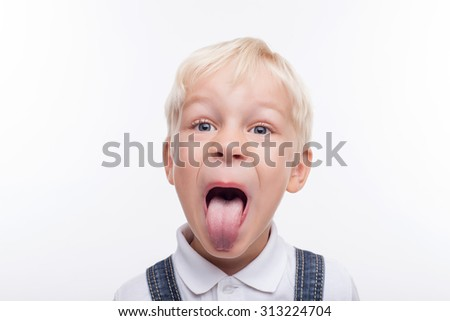Naughty boy is showing his tongue. He is looking at the camera with rebellion. Isolated and copy space in left side - stock photo