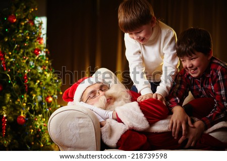 Naughty boys trying to wake Santa up - stock photo