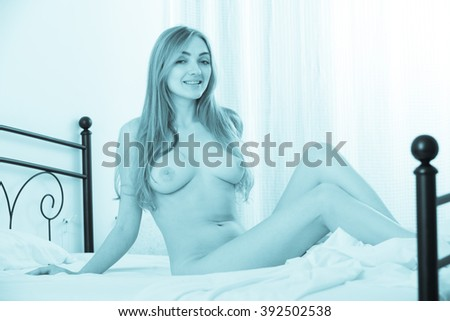 Naughty girl with sexy body lounging in bed, tonned - stock photo