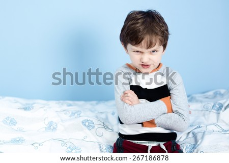 Naughty little boy. Angry little boy frowned while sitting in bed in pajama and looking at camera - stock photo