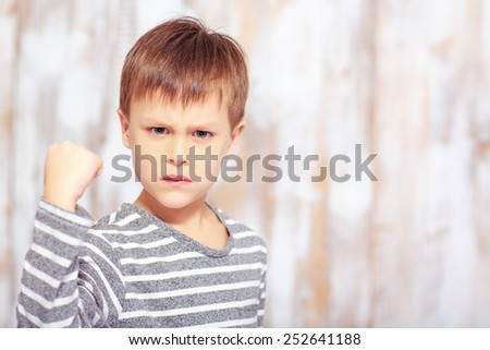 Naughty little boy. Angry little boy showing his fist while sitting in bed in pajama and looking at camera - stock photo