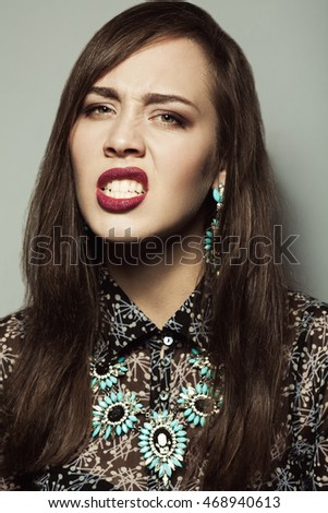 Naughty star, angry diva, femme fatale concept. Close up portrait of disturbed young woman wearing expensive luxurious earrings, necklace. Perfect shiny teeth. Long glossy chestnut hair. Studio shot