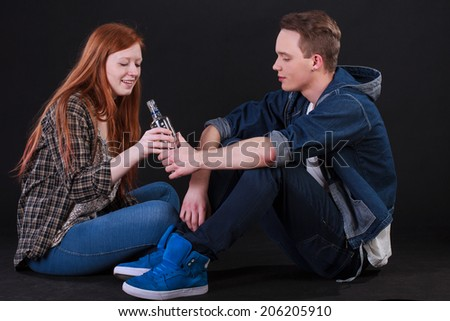 Naughty teenagers sitting on ground and drinking alcohol - stock photo
