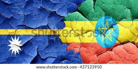 Nauru flag with Ethiopia flag on a grunge cracked wall - stock photo