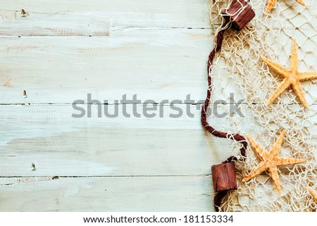 Nautical border formed of fishing net edged with corks entangled with scattered starfish on light beige wooden boards with copyspace for your text or advertisement - stock photo