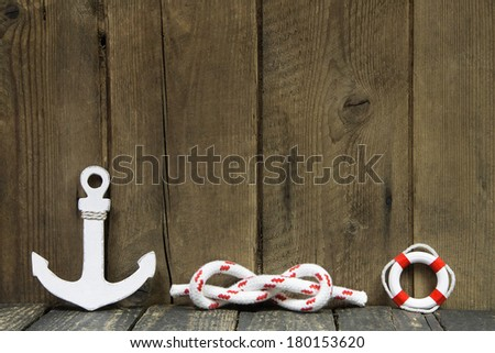 Nautical decoration with anchor and knot on a wooden background. - stock photo