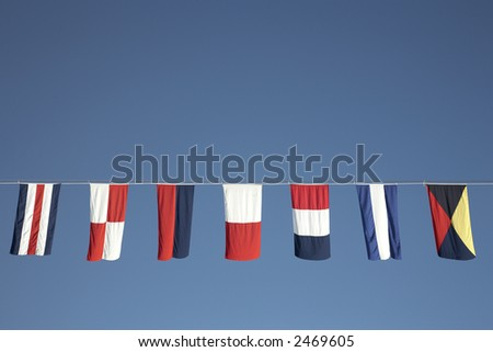 nautical flags strung along the line of a cruise ship - stock photo