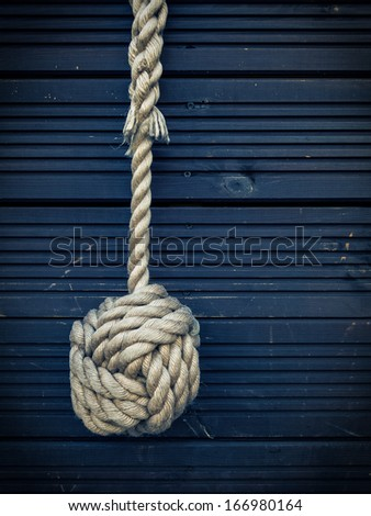 Nautical knot on a blue wooden background - stock photo