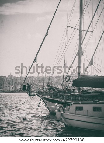 Nautical landscape with sailboat in retro style. Sea voyage on the yacht - luxury leisure and travel. Monochrome colors on film photo with vintage effect.