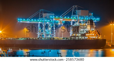 Nautical ship on a wharf during twilight is unloaded with huge modern cranes under colorful lighting - stock photo