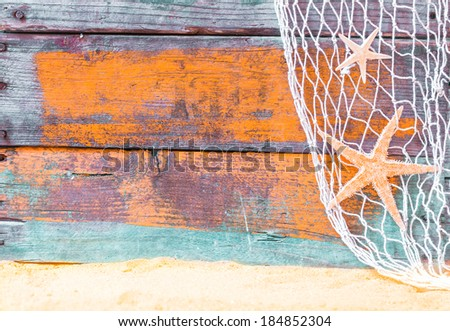 Nautical starfish background with rustic grunge weathered blue painted wooden boards, fishing net and golden beach sand, copyspace for text - stock photo