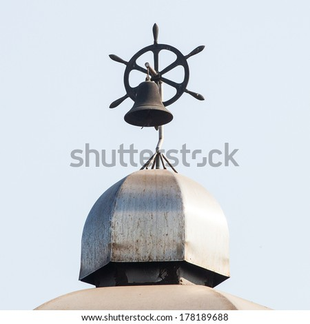 Nautical steering wheel and bell - stock photo