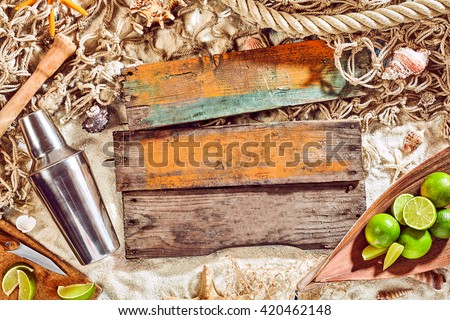 Nautical Themed Background with Copyspace - Cocktail Shaker, Limes and Blank Planks of Weathered Wood on Sand Surrounded by Fishing Net and Seashells - stock photo