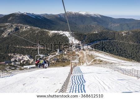 NAVACERRADA - JANUARY 4, 2015: Chair lift in Navacerrada Ski Resort, Navacerrada Mountain Pass, Madrid, Spain, on January 4, 2015. - stock photo