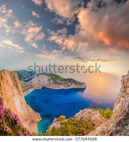Navagio beach with shipwreck and flowers against sunset on Zakynthos island in Greece - stock photo