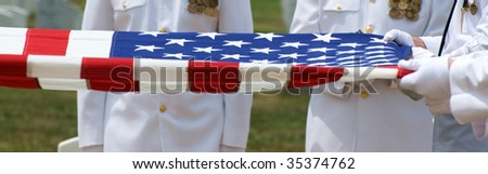 Naval Honor Guard at Arlington National Cemetery folding US Flag over casket - stock photo