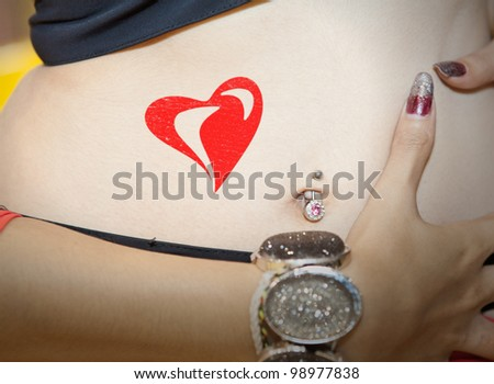 Navel of sport lady in athletes suit with jewels slide through and red heart. - stock photo