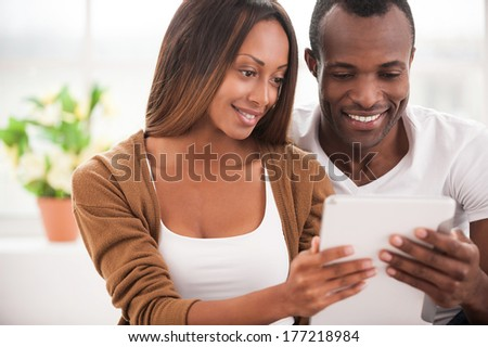 Navigating their new tablet together. Beautiful young African couple using digital tablet and smiling while sitting close to each other - stock photo
