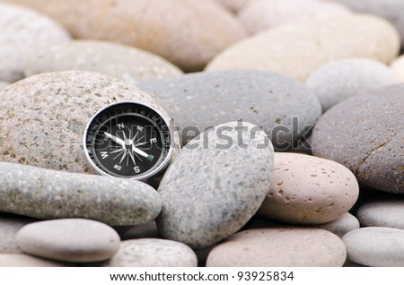 Navigation compass on stone pebbles - stock photo