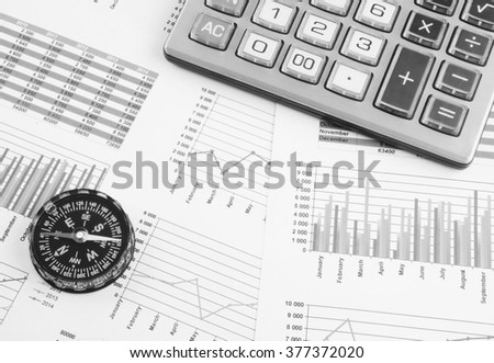 Navigation in financial world concept, calculator and compass on financial charts and graphs - stock photo
