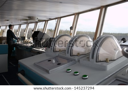 Navigational officer driving the ship on the river. Wide shot. - stock photo