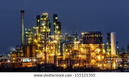 NAVODARI, ROMANIA - AUGUST 3: An illuminated oil and gas refinery plant at night on August 3, 2013 in Navodari, Romania. - stock photo