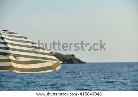 Navy look parasol on beach and sea in background