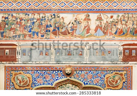 NAWALGARH, INDIA - FEB 6: Celebration crowds, musicians & wagons of train on naive style fresco of old mansion on February 6 2015. With pop. of 100000, Nawalgarh is education center of Shekhawati area - stock photo