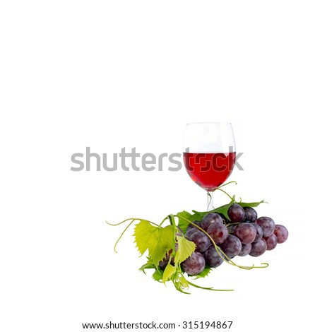 nch of red grapes and leaves and red wine glass against white background