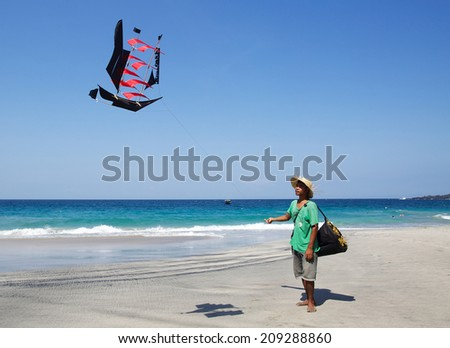 NDONESIA, BALI - JULY 07, 2014 - Balinese boy sells kites on the Bali beach, that was made by his father.