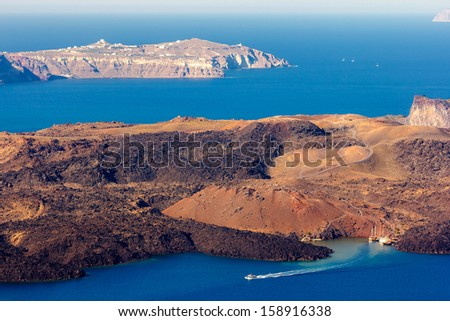 Nea Kameni volcanic island in Santorini Greece with little boat leaving the port photographed from a high point of view  - stock photo