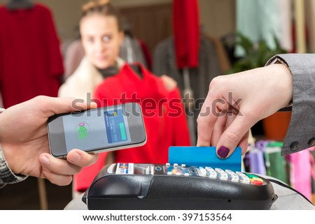 Near Field Communication - Man completing mobile Payment Woman shopping, male Hand holding cell Phone making instant Transaction at checkout Terminal Cashier credit Card female Customer on Background - stock photo