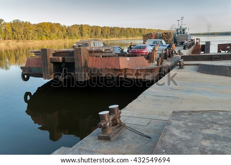 near Malmyzh, Russia - September 3, 2009: The car ferry cross Vyatka River and comes nearer to mooring - stock photo