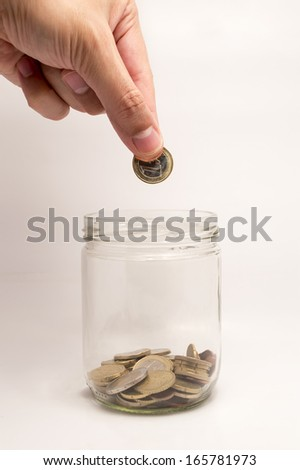 nearly empty jar with coins throwing hands inside and saving